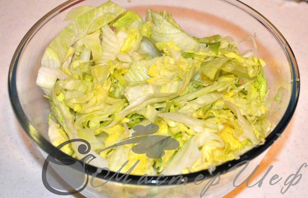 В нарезанны айсберг добавляем содержимое сковороды, перемешиваем, сбрызгиваем лимонным соком.
