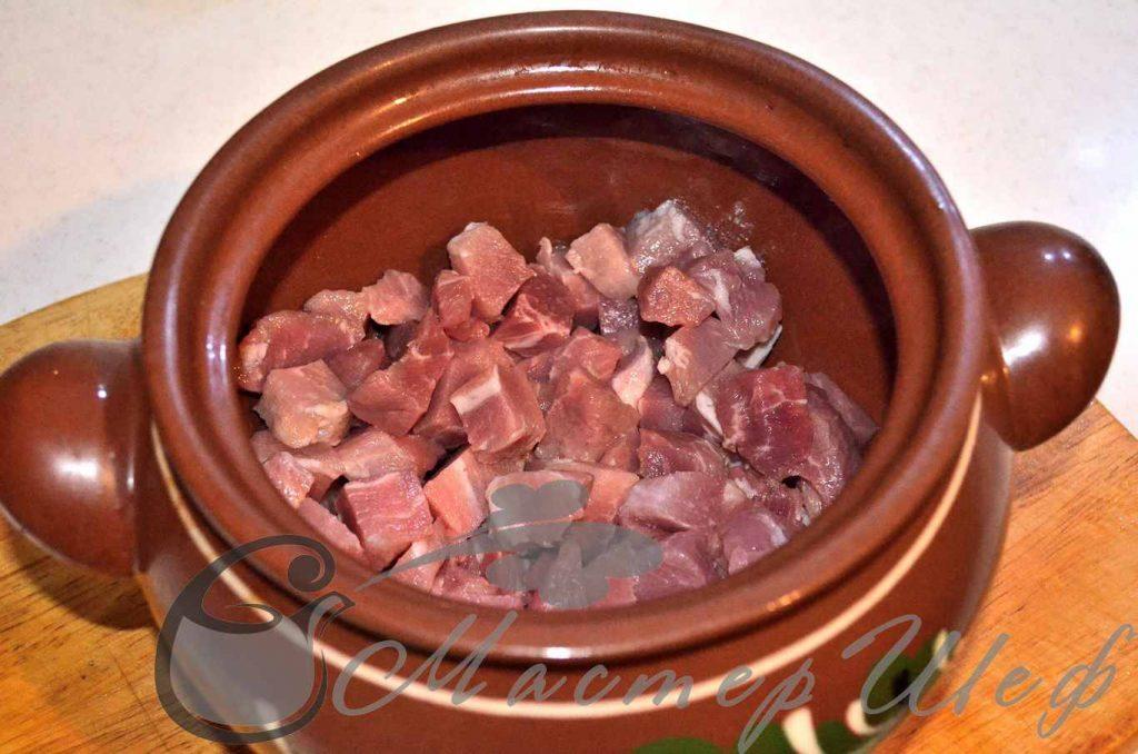 На дно горшочка наливаем масло, выкладываем мясо, добавляем соль, перец, хмели-сунели  и мелконарезанный лук