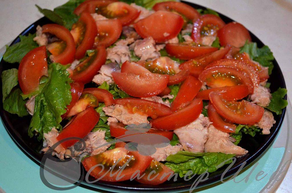 Рыбу рвем кусочками, помидоры нарезаем дольками, выкладываем все на салат