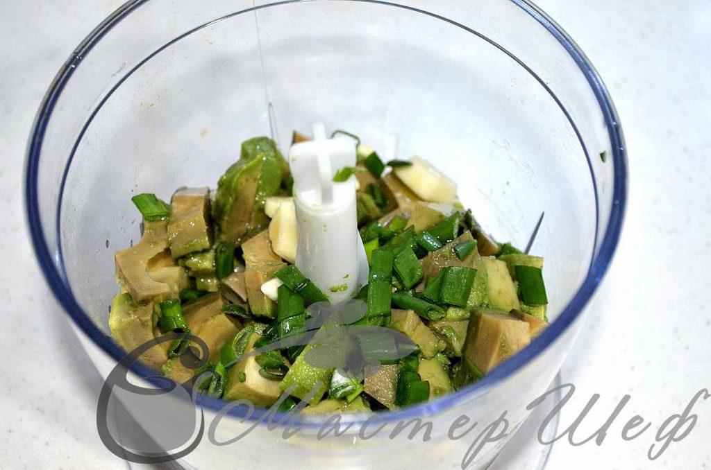 Нарезаем авокадо, добавляем нарезанный зеленый лук, чеснок и масло. Взбиваем до однородности.