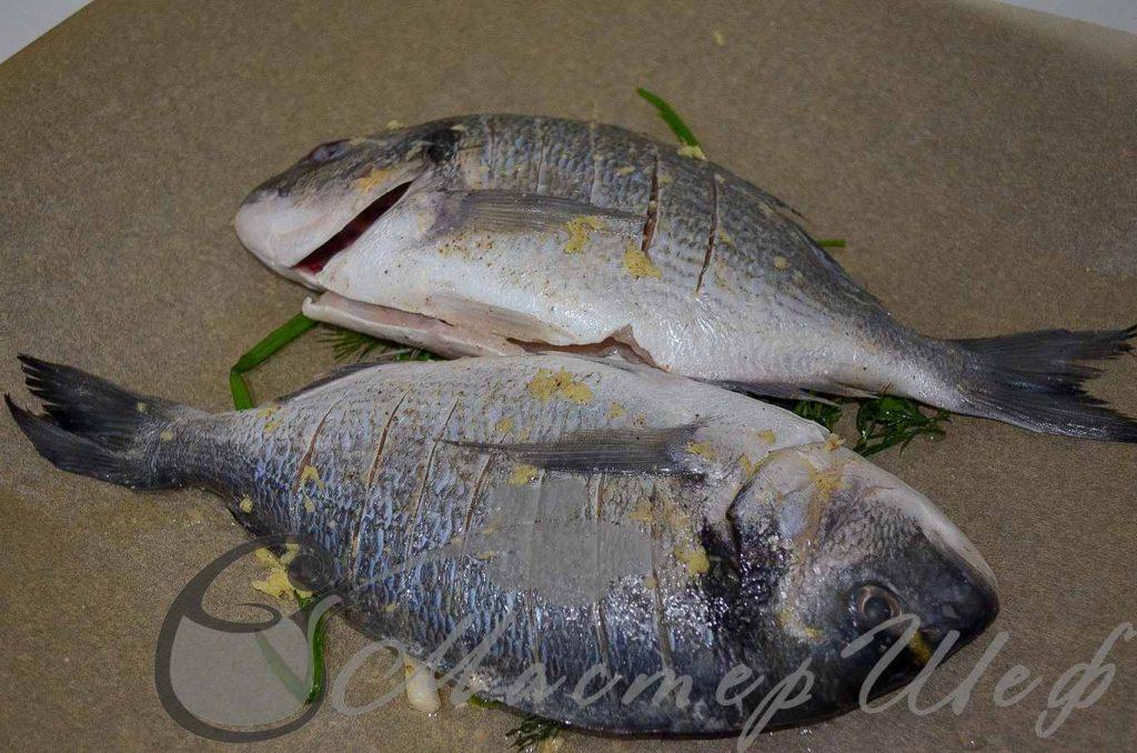 Кладем рыбу на зелень, смазываем ее маслом.