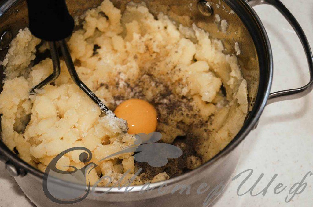 Сливаем воду, разминаем картофель. Добавляем желток, соль и перец.
